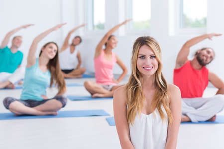 Yoga instructor sitting in front of a group that is stretching