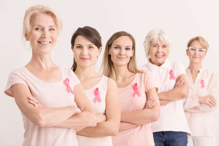 Breast cancer charity concept, diverse women united in cancer awareness mission wearing pink ribbons Stock Photo