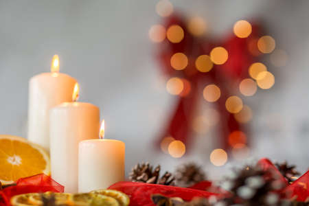 Close-up of white candles and orange as christmas time decoration Stock Photo