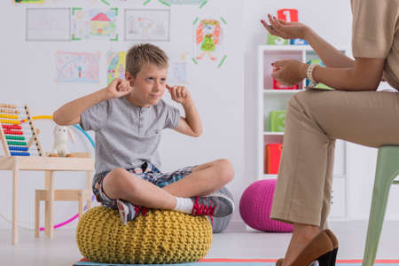 Young upset boy covering ears during therapy session with child psychologist Stock Photo