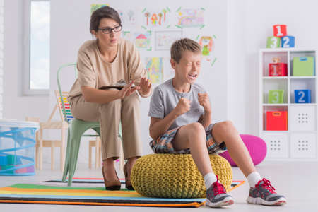 Temper tantrum concept, little angry emotional boy being aggressive during therapy session with child psychotherapist