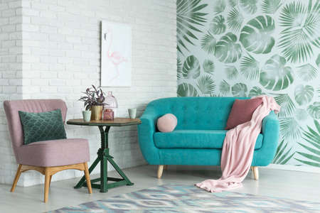 Green table with a plant between pink chair and blue sofa in floral living room with wallpaper and poster