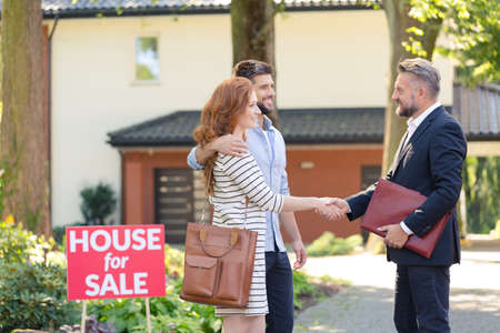 Seller congratulating a young couple buying house in suburbs Stock fotó
