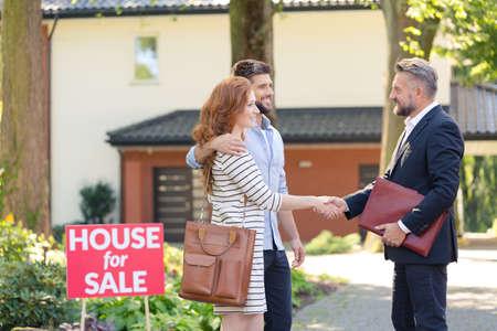 Verkoper die een jong paar feliciteert met het kopen van een huis in een buitenwijk Stockfoto