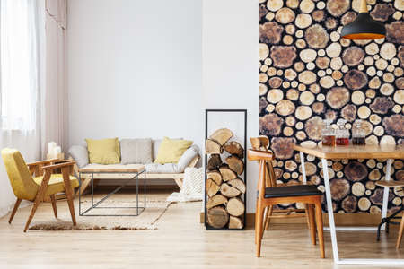 Modern licht appartement met beige bank, gele fauteuil, tafel en houten inrichting