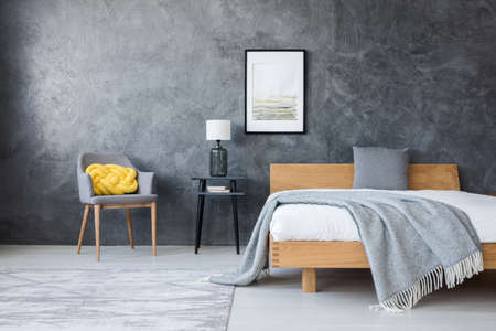 Poster on concrete wall above stool with lamp and wooden bed in dark bedroom with yellow pillow on a chair Foto de archivo