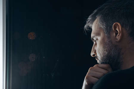 Man with beard holding his chin, standing beside a window at night