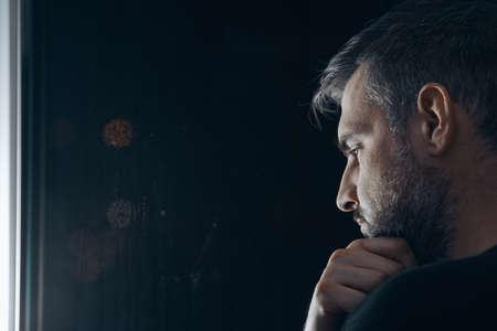 Mężczyzna z brodą trzymający się za brodę, stojący w nocy przy oknie