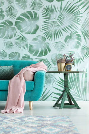 Pink blanket on blue settee next to a table with plant against leaves wallpaper in living room Foto de archivo