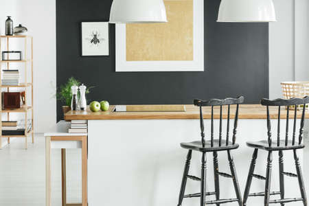 White lamps above wooden countertop with salt and pepper in room with black bar stools Stock Photo