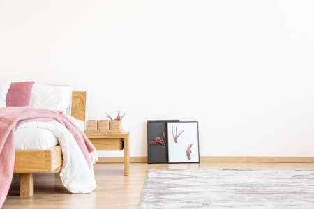DiY-posters naast een houten nachtkastje en bed met roze deken in slaapkamer met exemplaarruimte op lege muur