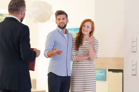 Young couple looking at interior of house for sale at a meeting with consultant