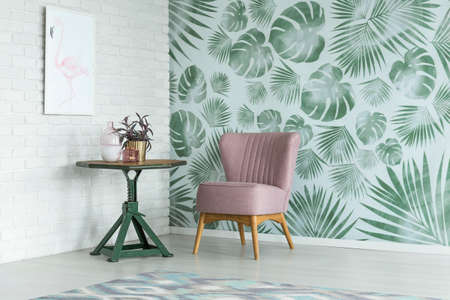 Pink chair at green table with a plant in gold pot in room with poster on white brick wall and floral wallpaper Stockfoto