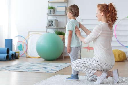 Vrouwelijke kindfysiotherapeut die de stekel van weinig patiënt in pediatrische orthopedische kliniek onderzoeken Stockfoto