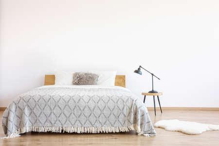 椅子に敷物とランプが付いているシンプルなベッドルームの毛皮の枕が付いているキングサイズのベッドのパターンの毛布