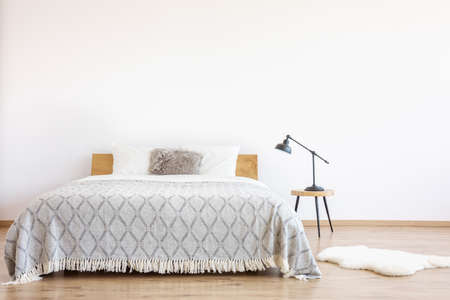 Patterned blanket on king-size bed with fur pillow in a simple bedroom with rug and lamp on stool