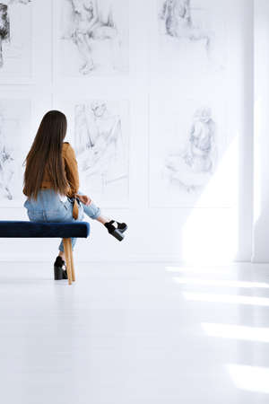 Student sitting on a bench in a fine arts academy room decorated with female nudity paintings Stock Photo