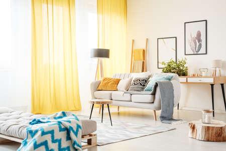 Gedessineerde deken op bank en kaars op houten stomp in ruime woonkamer met gele gordijnen en beige bank