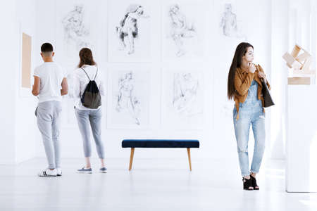 Exhibition of art such as paintings and a sculpture in a white gallery room interior