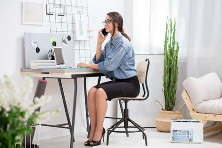 Virtual assistant sitting at home office and talking on the phone with her boss Standard-Bild