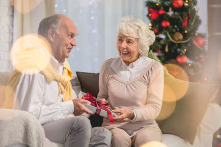 Senior female person giving present  with red bow to her senior  husband Stock Photo