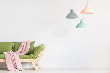 Pink blanket thrown on green wooden sofa in empty room with lamps