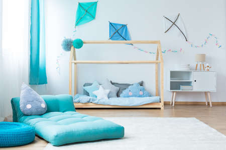 Blue mattress on white carpet in blue childs bedroom with DIY kites on the wall above cupboard and bed
