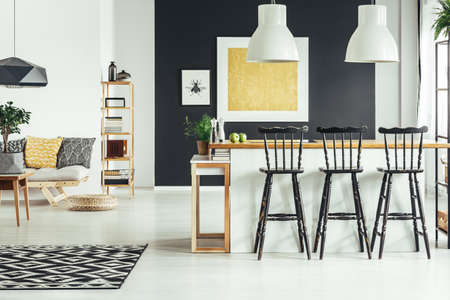 Geometric carpet in contemporary living room with black rustic bar stools at kitchen island