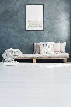 회색 벽에 포스터와 함께 방에 팔레트 침대에 배치 밝은 베개와 장식 쿠션 스톡 콘텐츠