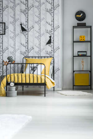 Decorative paper birds hanging on the wall with trees wallpaper in kids bedroom Stock Photo