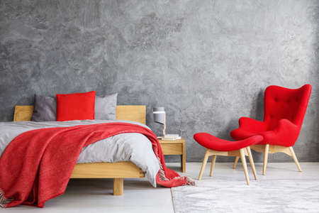 Red armchair and stool next to wooden bed against concrete wall with copy space in bedroom