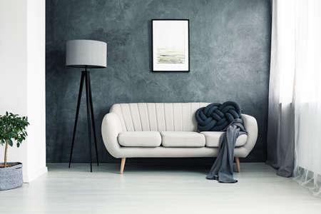 Sofá brilhante com almofada nó feito à mão e manta cinza em pé em uma sala de estar com lâmpada e cartaz pendurado na parede texturizada