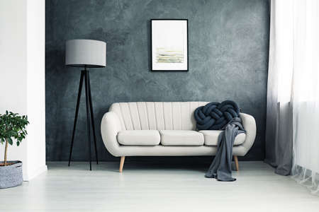 Bright couch with handmade knot cushion and grey blanket standing in a living room with lamp and poster hanging on textured wall Foto de archivo