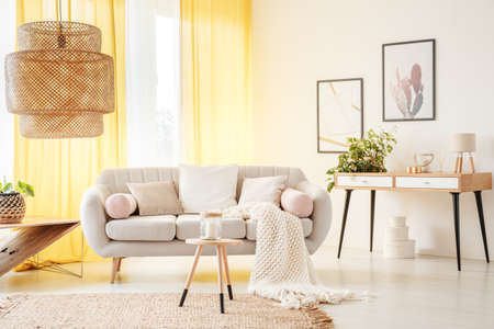 Rattan lamp and wooden stool on carpet in warm bohemian living room with yellow curtains and beige settee with white pillows Stock Photo