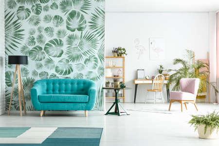 Ruime kamer met lamp naast blauwe bank tegen groen behang en roze stoel in de buurt van werkruimte