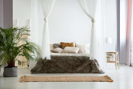 Witte muren en bont beddengoed in gezellige warme slaapkamer met Boheemse design, planten en aarde kleurenschema