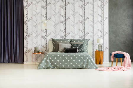 キングサイズのベッド、森林をモチーフにした広々 としたベッドルームで銅のテーブルの近くの椅子にピンクの毛布 写真素材