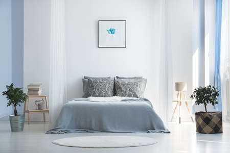 Soft textiles and potted plants in light blue master bedroom with minimalist bohemian interior design  Banque d'images