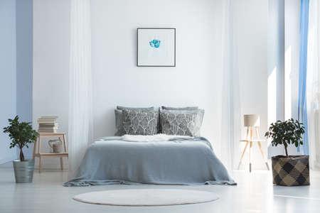 Zacht textiel en potplanten in lichtblauwe hoofdslaapkamer met minimalistisch Boheems interieur
