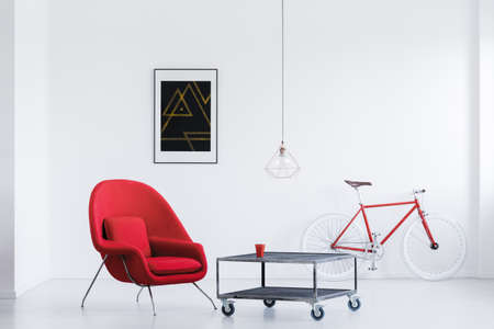 Black poster on white wall in bright studio with bike and red armchair at industrial table Stok Fotoğraf