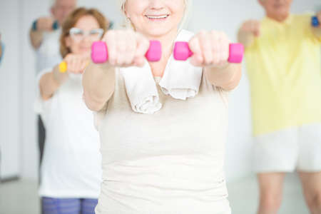 Close-up of smiling elderly person working out with pink dumbbells