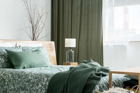 Green blanket on king-size bed with floral bedsheets in bedroom with olive curtain and lamp on stool