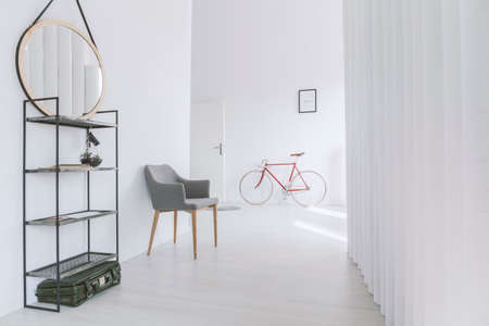 Mirror on shelf next to grey chair in minimalist corridor with red bicycle against wall with poster