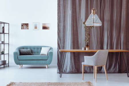 Glass lampshade hanging above wood and metal table standing in white living room with couch and curtain