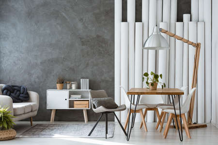 Designer lamp above dining table in monochromatic living room with paper tubes, sofa and cupboard