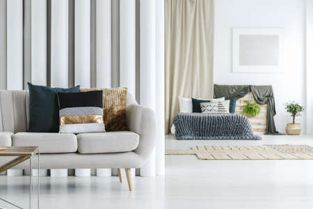Grey sofa with three decorative cushions in a photo with bed in blurred background Stock Photo