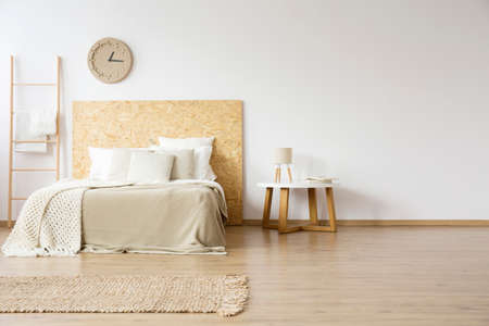 Lamp on wooden table next to bed with pillows in natural bedroom with ladder, paper clock and rug