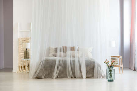 Modern homely bedroom interior in calm neutral colors with canopy over king-size bed and glass vase with flowers 스톡 콘텐츠