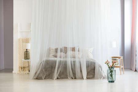 Nowoczesne, przytulne wnętrze sypialni w spokojnych, neutralnych kolorach z baldachimem nad łóżkiem king-size i szklanym wazonem z kwiatami
