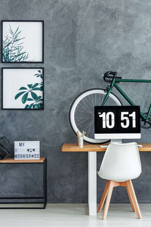 Living room with grey raw wall and simple workspace with bike placed on desk